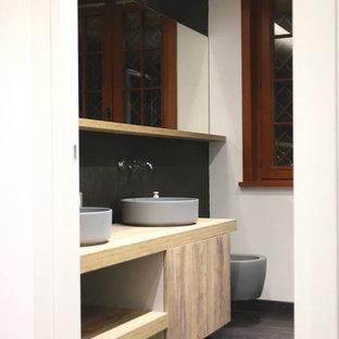 Неиссякаемый источник вдохновения для домашнего уюта: большой туалет в современном стиле с плоскими фасадами, светлыми деревянными фасадами, инсталляцией, черной плиткой, черными стенами, паркетным полом среднего тона, настольной раковиной, столешницей из ламината и коричневым полом