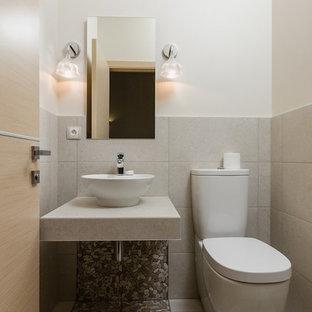 На фото: маленький туалет в стиле кантри с унитазом-моноблоком, бежевой плиткой, керамогранитной плиткой, белыми стенами, полом из галечной плитки и настольной раковиной с