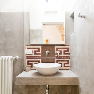 Idee per un bagno di servizio mediterraneo con top in cemento
