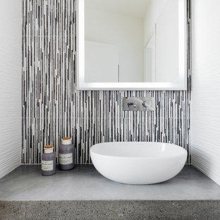 На фото: туалет в современном стиле с разноцветной плиткой, удлиненной плиткой, настольной раковиной, столешницей из бетона, серой столешницей и разноцветными стенами с