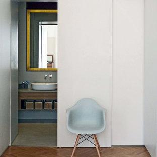 Ejemplo de aseo contemporáneo, de tamaño medio, con armarios con paneles lisos, puertas de armario de madera clara, sanitario de dos piezas, paredes grises, suelo de madera en tonos medios, lavabo sobreencimera, encimera de cemento, suelo amarillo y encimeras grises