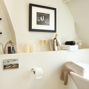 オックスフォードシャーの小さいおしゃれなトイレ・洗面所 (オープンシェルフ、淡色木目調キャビネット、壁掛け式トイレ、ベージュのタイル、ベージュの壁、磁器タイルの床、壁付け型シンク、ベージュの床、表し梁) の写真
