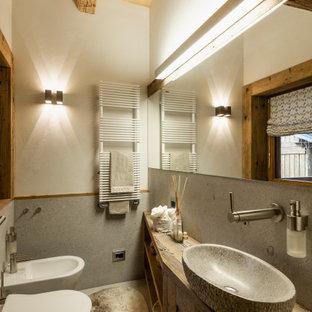 中サイズのラスティックスタイルのおしゃれなトイレ・洗面所 (落し込みパネル扉のキャビネット、中間色木目調キャビネット、壁掛け式トイレ、グレーのタイル、ライムストーンタイル、白い壁、ベッセル式洗面器、木製洗面台、ライムストーンの床) の写真