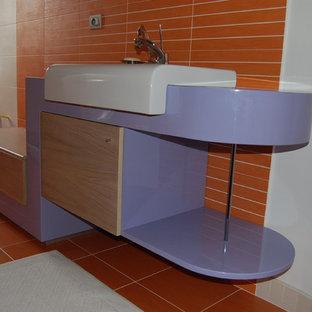 На фото: большой туалет в современном стиле с фиолетовыми фасадами, инсталляцией, оранжевой плиткой, керамогранитной плиткой, оранжевыми стенами, полом из керамогранита, настольной раковиной, столешницей из дерева, оранжевым полом и фиолетовой столешницей с