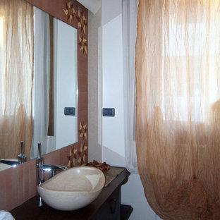 Стильный дизайн: туалет среднего размера в современном стиле с плоскими фасадами, темными деревянными фасадами, раздельным унитазом, терракотовой плиткой, белыми стенами, полом из терраццо, настольной раковиной, столешницей из дерева, бежевым полом и коричневой столешницей - последний тренд