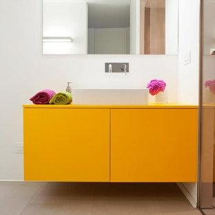 Foto de aseo contemporáneo, pequeño, con armarios con paneles lisos, puertas de armario amarillas, sanitario de pared, paredes blancas, suelo de baldosas de porcelana, lavabo sobreencimera, encimera de madera y encimeras naranjas