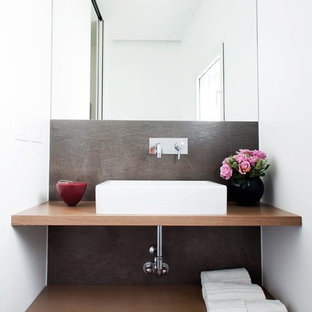 На фото: маленький туалет в современном стиле с открытыми фасадами, светлыми деревянными фасадами, серой плиткой, белыми стенами, полом из керамогранита, настольной раковиной, столешницей из дерева, биде, плиткой из листового камня и коричневой столешницей с