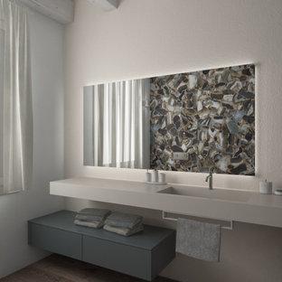 Mittelgroße Moderne Gästetoilette mit flächenbündigen Schrankfronten, grauen Schränken, Wandtoilette mit Spülkasten, farbigen Fliesen, Porzellanfliesen, grauer Wandfarbe, braunem Holzboden, integriertem Waschbecken, beigem Boden, beiger Waschtischplatte, schwebendem Waschtisch und freigelegten Dachbalken in Venedig