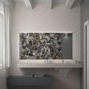 ヴェネツィアの中くらいのモダンスタイルのおしゃれなトイレ・洗面所 (フラットパネル扉のキャビネット、グレーのキャビネット、分離型トイレ、マルチカラーのタイル、磁器タイル、グレーの壁、無垢フローリング、一体型シンク、ベージュの床、ベージュのカウンター、フローティング洗面台、表し梁) の写真