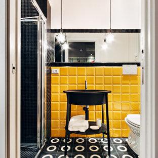 Aménagement de petits WC et toilettes contemporains avec des portes de placard noires, un carrelage jaune, des carreaux de céramique, béton au sol, un sol noir et un placard sans porte.