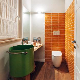Idee per un piccolo bagno di servizio design con piastrelle arancioni, piastrelle in ceramica, parquet scuro, WC sospeso, pareti bianche e pavimento marrone