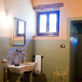 Foto di un bagno di servizio country di medie dimensioni con ante in legno bruno, piastrelle in terracotta, pareti verdi, pavimento in terracotta, lavabo integrato, top in pietra calcarea e piastrelle multicolore