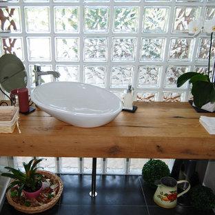 Стильный дизайн: маленький туалет в стиле модернизм с стеклянными фасадами, коричневыми фасадами, раздельным унитазом, серой плиткой, серыми стенами, полом из линолеума, настольной раковиной, столешницей из дерева, черным полом и коричневой столешницей - последний тренд
