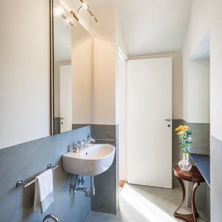 Cette image montre un WC et toilettes marin de taille moyenne avec un mur multicolore, béton au sol, un lavabo suspendu, un sol gris et un bidet.