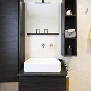 ヴェネツィアの中くらいのインダストリアルスタイルのおしゃれなトイレ・洗面所 (オープンシェルフ、茶色いキャビネット、分離型トイレ、ベージュのタイル、ベージュの壁、磁器タイルの床、ベッセル式洗面器、ラミネートカウンター、グレーの床、ブラウンの洗面カウンター) の写真