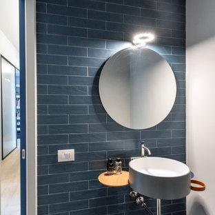 Foto di un piccolo bagno di servizio minimal con WC sospeso, piastrelle blu, piastrelle in gres porcellanato, pareti blu, pavimento in gres porcellanato, lavabo sospeso e pavimento grigio