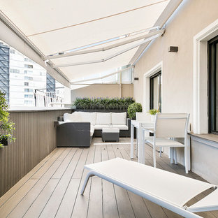 Photo of a medium sized modern terrace and balcony in Barcelona with an awning and a potted garden.