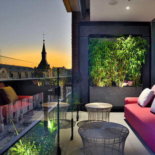 Design ideas for a contemporary apartment glass railing balcony in Madrid with a roof extension.