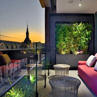 Diseño de balcones contemporáneo, en anexo de casas, con jardín de macetas y barandilla de vidrio