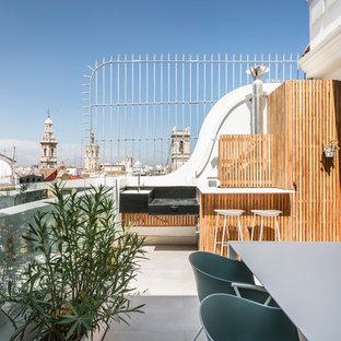 Ejemplo de balcones mediterráneo, de tamaño medio, sin cubierta, con jardín de macetas y barandilla de vidrio