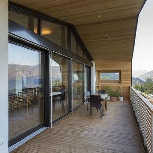 Foto di terrazze e balconi moderni con un giardino in vaso, un tetto a sbalzo e parapetto in legno