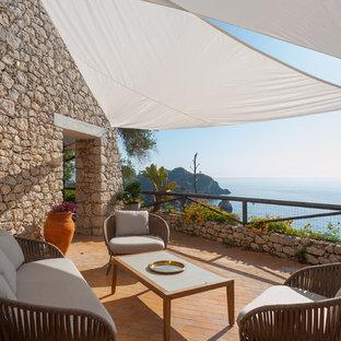 Foto di terrazze e balconi mediterranei con un parasole