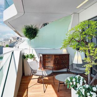 Immagine di terrazze e balconi contemporanei di medie dimensioni con un giardino in vaso, un tetto a sbalzo e parapetto in vetro