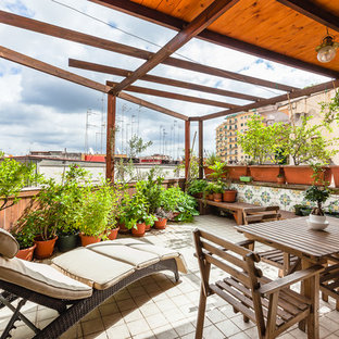 Ispirazione per terrazze e balconi mediterranei di medie dimensioni con un parasole, parapetto in legno e un giardino in vaso