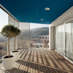 Esempio di grandi terrazze e balconi contemporanei con un tetto a sbalzo, parapetto in metallo e un giardino in vaso