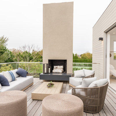 Balcony - huge contemporary glass railing balcony idea in New York with a fire pit and no cover