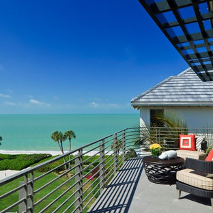 Example of an island style balcony design in Miami with an awning