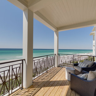Example of a coastal balcony design in Miami with a roof extension