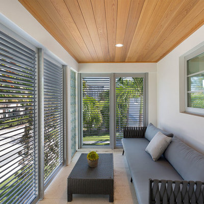 Mid-sized trendy glass railing balcony photo in Miami with a roof extension