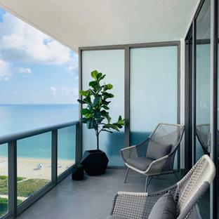 Exemple d'un balcon moderne d'appartement avec une extension de toiture et un garde-corps en matériaux mixtes.