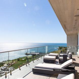 Idee per terrazze e balconi minimal con un tetto a sbalzo e parapetto in vetro