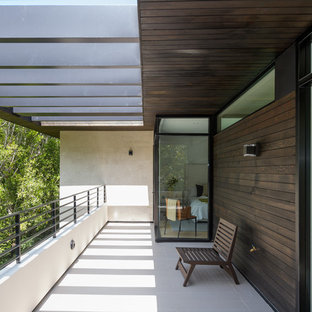 Example of a minimalist mixed material railing balcony design in Los Angeles with a pergola