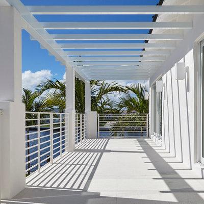 Large trendy balcony photo in Miami with a pergola