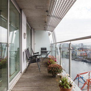 This is an example of a contemporary mixed railing balcony in Manchester with an awning.