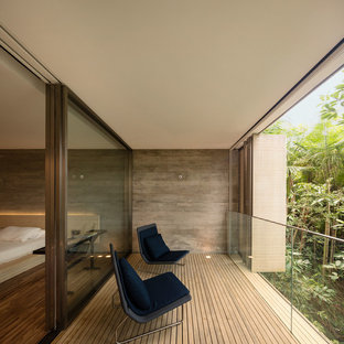 Inspiration pour un très grand balcon minimaliste avec une extension de toiture et des solutions pour vis-à-vis.