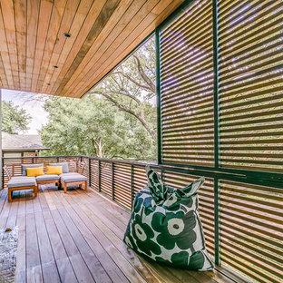 Esempio di un privacy sul balcone minimalista di medie dimensioni con un tetto a sbalzo e parapetto in materiali misti