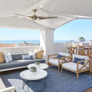 Ispirazione per terrazze e balconi costieri con un giardino in vaso, un tetto a sbalzo e parapetto in legno