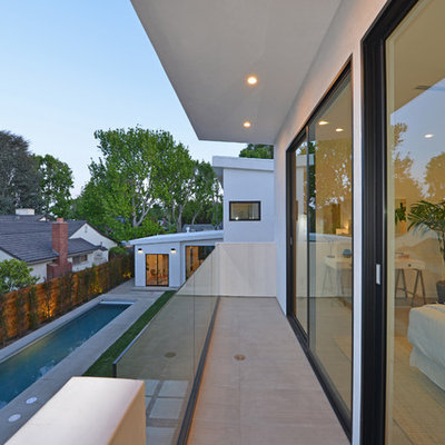 Inspiration for a mid-sized contemporary balcony remodel in Los Angeles with a roof extension