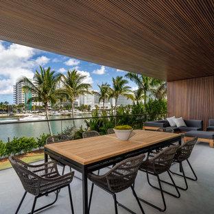 Idee per terrazze e balconi stile marino con un tetto a sbalzo e parapetto in vetro