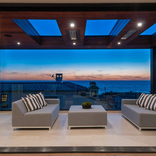 Photo of a contemporary balcony in Los Angeles with a pergola and glass railing.