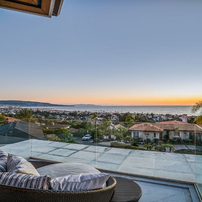 Large trendy glass railing balcony photo in Los Angeles with a roof extension