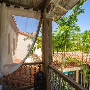 Пример оригинального дизайна: большой балкон и лоджия в средиземноморском стиле с навесом и деревянными перилами