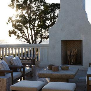 Ví dụ về thiết kế ban công tuscan ở Santa Barbara với lò sưởi và không có nắp