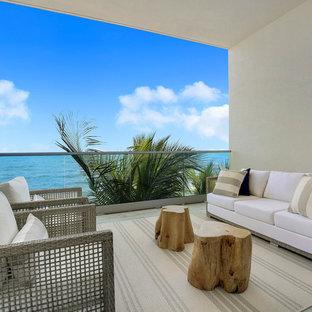 Esempio di terrazze e balconi costieri con un tetto a sbalzo e parapetto in materiali misti