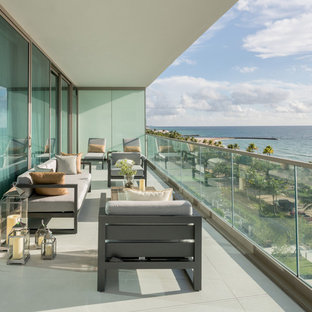 Inspiration for a mid-sized contemporary glass railing balcony remodel in Miami with a roof extension