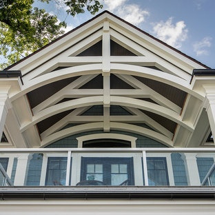Example of a large arts and crafts mixed material railing balcony design in Detroit with a roof extension